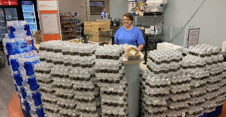 employee_surrounded_by_cases_of_bottled_water.jpg