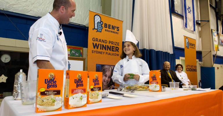 KID CUISINE Bens Beginners winner Sydney Fialkow prepares her Chicken and Rice dish with the help of Culinary Innovation Manager Chris Skolmutch of Uncle Bens parent Mars Food US
