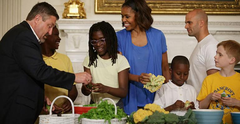 US First Lady Michelle Obama and West Virginia Department of Education Office of Child Nutrition Executive Director Richard Goff help students from five District of Columbia schools make a meal using the summer crop from the White House Kitchen Garden in the State Dining Room at the White House June 12