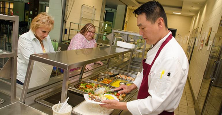 UMass Dining Chef de Cuisine Anthony Jung serves the administrative staff during a test run at Chicopee Comprehensive High School
