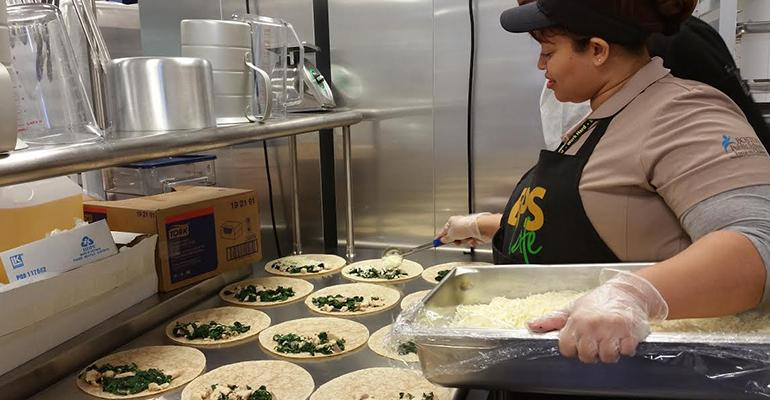 Fenway cafeteria staff working with a Project Bread chef on chicken and spinach quesadillas