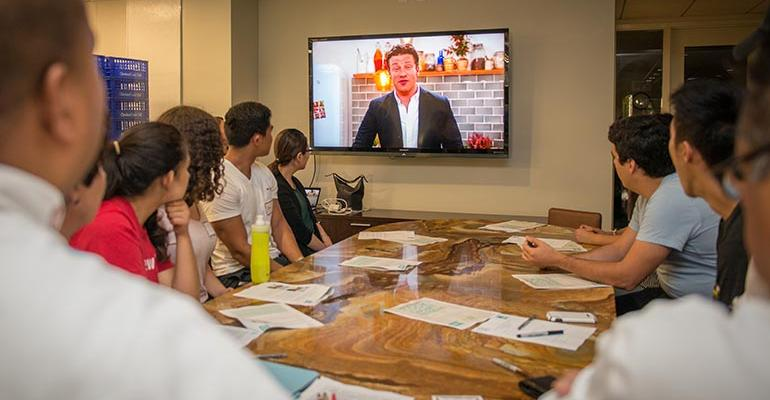 Students watch a video from Jamie Oliver at the beginning of the program