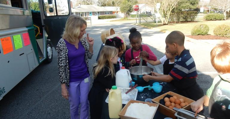 Second grade teacher Monique Ellington of Winter Park Elementary School helps her students prepare sweet potato batter for pancakes during the UNCWilmington food truck cooking demo event at the school