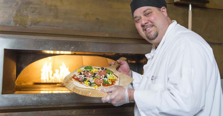 Executive Chef Victor Schmidt of CulinArt Group readies a pizza at Tartans Pizza one of the dining concepts on the Carnegie Mellon campus now accepting preorders through the GET Food application