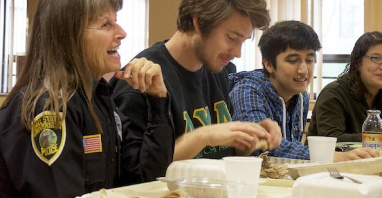 A Balll State campus security officer shares a meal with students as part of a new community policing approach aided in part by a dining service program that foots the bill for the meals