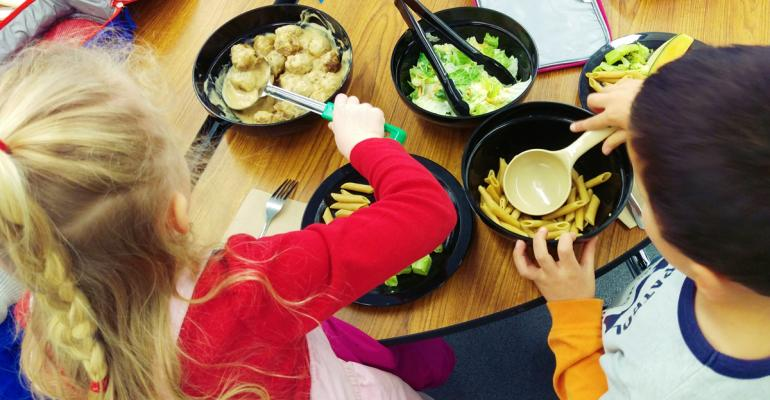 Students at Minneapolis Schools39 Webster Elementary serve themselves from communal platters while sitting at tables rather than going through a traditional serving line